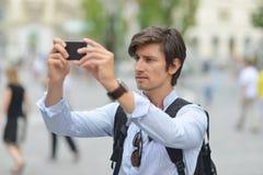 Junger gutaussehender Mann, der mit intelligentem Mobiltelefon fotografiert Stockbild