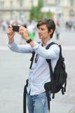 Junger gutaussehender Mann, der mit intelligentem Mobiltelefon fotografiert Lizenzfreie Stockfotos