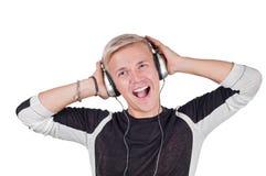 Junger gutaussehender Mann, der mit Kopfhörern singt Stockbild