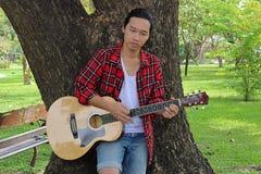 Junger gutaussehender Mann, der Musik auf Akustikgitarre im Park spielt Lizenzfreie Stockbilder