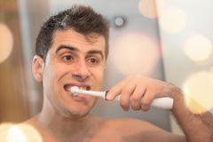 Junger gutaussehender Mann, der seine Zähne putzt lizenzfreie stockfotos