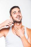 Junger gutaussehender Mann, der seinen Bart trimmt Stockfotografie