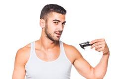 Junger gutaussehender Mann, der seinen Bart trimmt Stockbild