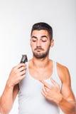 Junger gutaussehender Mann, der seinen Bart trimmt Stockfotos