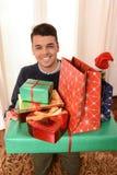 Junger gutaussehender Mann, der Weihnachtsgeschenke hält lizenzfreie stockfotos