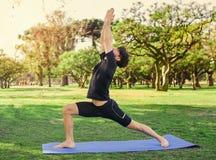Junger gutaussehender Mann, der Yoga im Park tut Lizenzfreies Stockbild