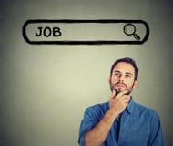 Junger gutaussehender Mann des Headshot, der nach einem neuen Job suchend denkt Lizenzfreies Stockfoto