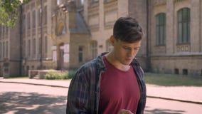 Junger gutaussehender Mann geht durch Straße in der Tageszeit im Sommer und klopft auf dem Smartphone und nennt, Kommunikationsko stock video