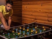 Junger gutaussehender Mann im gelben T-Shirt, das auf Fußball spielt lizenzfreies stockbild