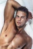Junger gutaussehender Mann im Schlafzimmer Stockbild