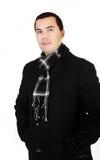 Junger gutaussehender Mann im schwarzen Mantel und im Schal getrennt lizenzfreie stockbilder