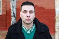 Junger gutaussehender Mann im schwarzen Winter-Mantel, der einen Kuss sendet Stockfotografie