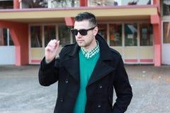 Junger gutaussehender Mann im schwarzen Winter-Mantel, der Sonnenbrille entfernt Lizenzfreies Stockfoto