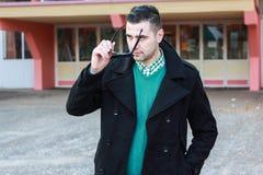 Junger gutaussehender Mann im schwarzen Winter-Mantel, der Sonnenbrille entfernt stockbild