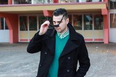 Junger gutaussehender Mann im schwarzen Winter-Mantel, der Sonnenbrille entfernt Stockbilder