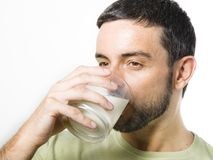 Junger gutaussehender Mann mit Bart-Trinkmilch stockbilder