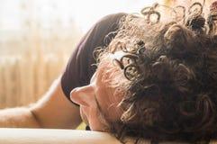 Junger gutaussehender Mann mit dem gelockten Haar schlafend auf der Couch lizenzfreie stockfotos
