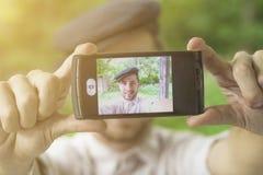 Junger gutaussehender Mann mit der Kappe, die Selbst mit Telefon nimmt Stockbild