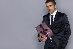 Junger gutaussehender Mann mit einem Geschenk Stockbilder