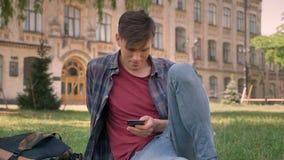 Junger gutaussehender Mann sitzt auf Gras im Park und passt Seiten im Internet auf dem Smartphone auf und passt an der Kamera auf stock video