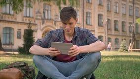 Junger gutaussehender Mann sitzt auf Gras im Park und passt Seiten im Internet auf der Tablette auf und passt an der Kamera auf,  stock video