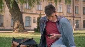 Junger gutaussehender Mann sitzt auf Gras im Park und passt Seiten im Internet auf Smartphone auf, sich entspannen Konzept, Kommu stock video