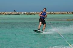 Junger Guy Riding Goofy On ein Wakeboard in Aruba lizenzfreies stockfoto