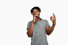 Junger hübscher afrikanischer Mann, der im Mikrofon über weißem Hintergrund singt Lizenzfreies Stockbild