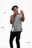 Junger hübscher afrikanischer Mann, der im Mikrofon über weißem Hintergrund singt Lizenzfreie Stockbilder