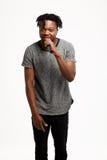 Junger hübscher afrikanischer Mann, der im Mikrofon über weißem Hintergrund singt Lizenzfreies Stockfoto