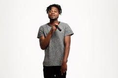 Junger hübscher afrikanischer Mann, der im Mikrofon über weißem Hintergrund singt Stockfotos