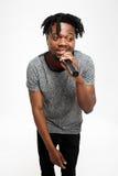 Junger hübscher afrikanischer Mann, der im Mikrofon über weißem Hintergrund singt Stockbilder