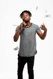 Junger hübscher afrikanischer Mann, der im Mikrofon über weißem Hintergrund singt Stockbild