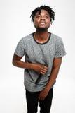 Junger hübscher afrikanischer Mann, der im Mikrofon über weißem Hintergrund singt Stockfotografie