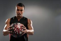 Junger hübscher afrikanischer Mann, der mit Basketball aufwirft Lizenzfreies Stockfoto