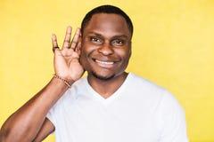 Junger hübscher Afroamerikanermann, der versucht, besseres durch die Befestigung seiner Palme zum Ohr zu hören stockbilder