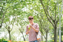 Junger hübscher asiatischer Mann, der öffentlich seinen intelligenten Park des Telefons genießt Stockfotos