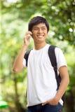 Junger hübscher asiatischer Student, der am Handy spricht Lizenzfreie Stockbilder