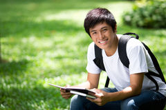 Junger hübscher asiatischer Student mit Laptop stockfotos