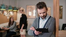 Junger hübscher bärtiger Mann benutzt Tablette des Bildschirm- im modernen Startbüro Stockfotos