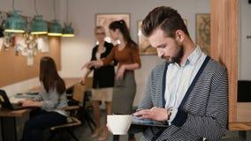 Junger hübscher bärtiger Mann benutzt Tablette des Bildschirm- und trinkenden Kaffee im modernen Startbüro Stockbilder