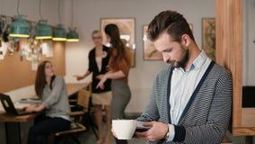 Junger hübscher bärtiger Mann benutzt Tablette des Bildschirm- und trinkenden Kaffee im modernen Startbüro Lizenzfreies Stockbild