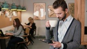 Junger hübscher bärtiger Mann benutzt Tablette des Bildschirm- und trinkenden Kaffee im modernen Startbüro Lizenzfreie Stockfotos