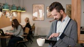 Junger hübscher bärtiger Mann benutzt Tablette des Bildschirm- und trinkenden Kaffee im modernen Startbüro Stockfotos