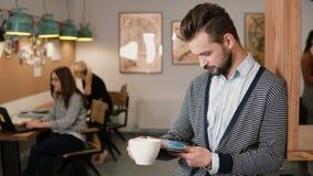 Junger hübscher bärtiger Mann benutzt Tablette des Bildschirm- und trinkenden Kaffee im modernen Startbüro Lizenzfreie Stockbilder