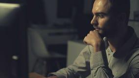 Junger hübscher Büroangestellter, der Computer nachts verwendet stock footage