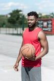Junger hübscher Basketball-Spieler, der in der Hand Ball hält Stockfoto