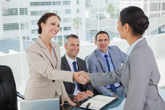 Junger hübscher Bewerber, der Hände mit zukünftigen Arbeitgebern rüttelt Lizenzfreie Stockfotos