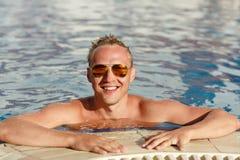 Junger hübscher blonder Mann in der Sonnenbrille im Pool emotional L Lizenzfreie Stockfotos