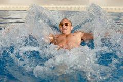 Junger hübscher blonder Mann in der Sonnenbrille taucht im Pool in Stockfotografie